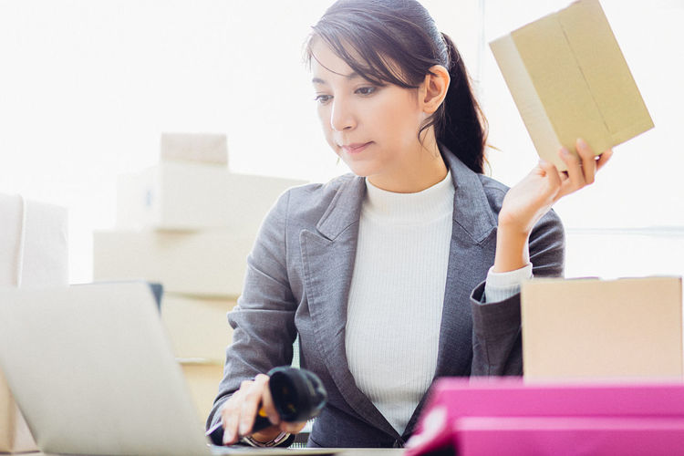 Woman using laptop while holding package and bar code scanner