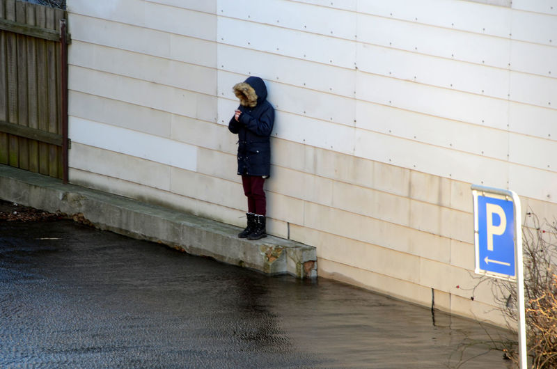 Unidentificable boy stands on a concrete socked watching the floods of a storm surge. Architecture Water Real People Men Alone Caught Handy Day Flood Standing Outdoors Sign Clothing Communication Front View Lifestyles Full Length One Person Casual Clothing Leisure Activity Building Exterior Built Structure Wall - Building Feature Storm Surge