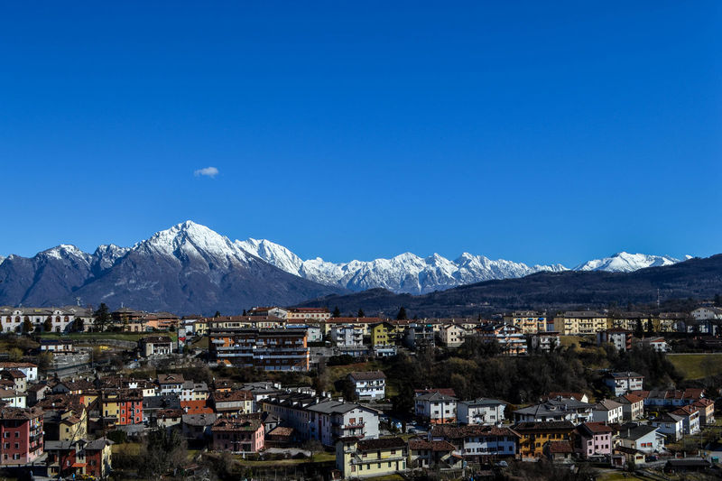 Buildings In Town By Mountains Against Clear Blue Sky