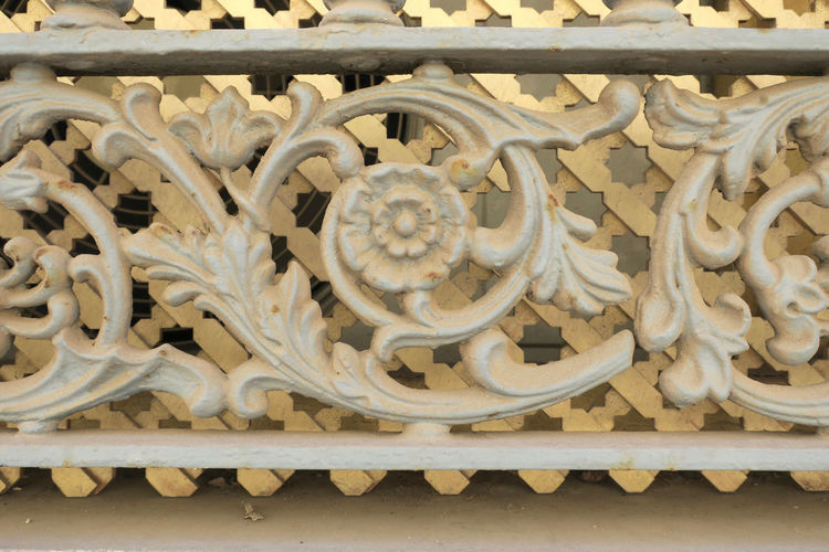 white painted cast iron fence Architecture Art And Craft No People Craft Built Structure Carving - Craft Product Creativity Pattern Day The Past Close-up History Design Sculpture Representation Metal Gate Travel Destinations Building Exterior Travel Ornate Floral Pattern Carving Wrought Iron