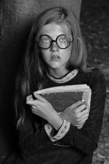 Portrait of girl in eyeglasses holding old book at home