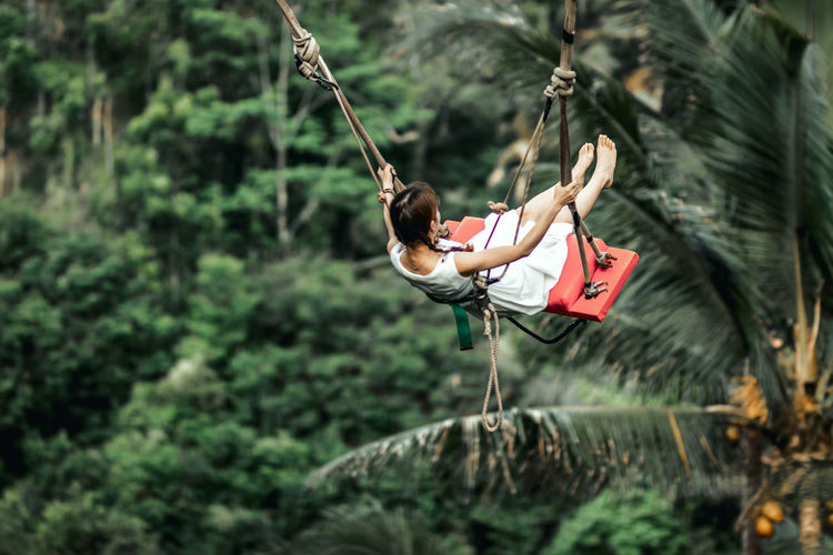 Midsection of woman hanging on rope in forest