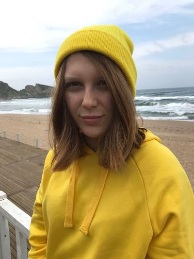 Portrait of young woman standing at beach