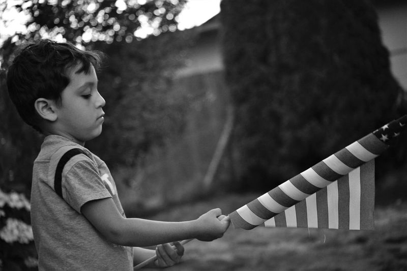 Side view of boy holding american flag while standing in yard
