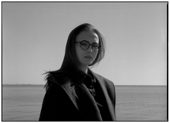 A series of black and white photos on the beach in a winter sunny day. Shooting by the sea. Portraits with natural light. Candid Authentic Moments Authentic Lifestyles Lifestyle Blackandwhite Black And White Glasses One Person Eyeglasses  Real People Portrait Front View Headshot Sky Young Adult Sea Standing Women Leisure Activity Water Looking Hairstyle Contemplation Human Face