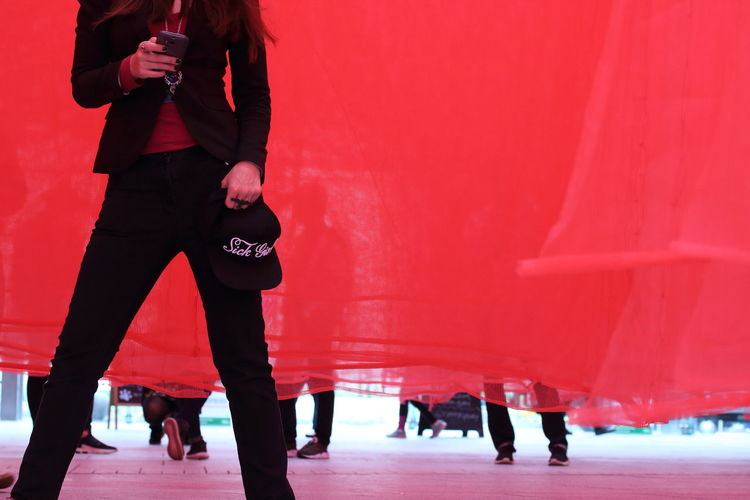 Midsection of woman using mobile phone while standing against red curtain