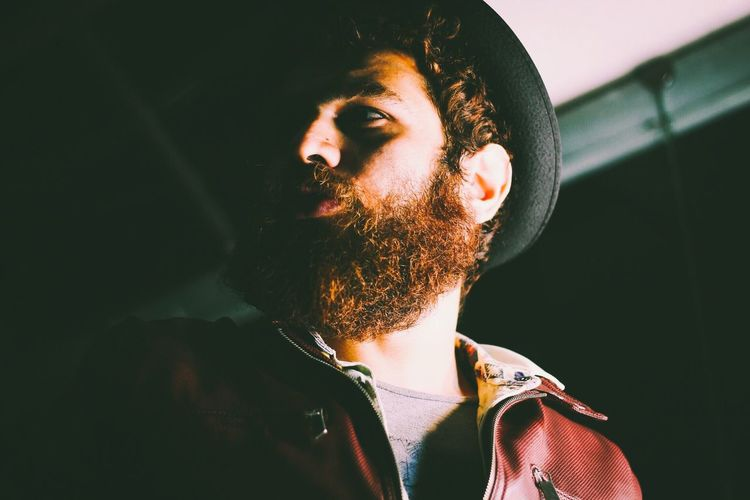 Low Angle View Of Bearded Man Looking Away In Darkroom