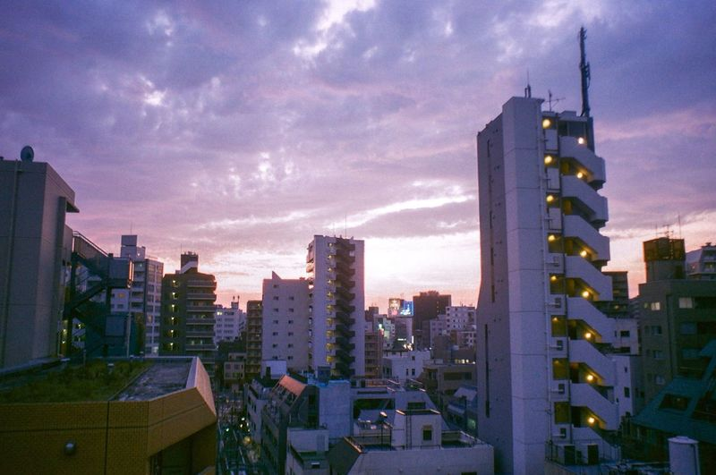Buildings in city against sky during sunset
