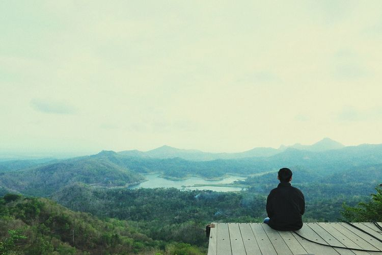 Rear view of man looking at mountain while sitting on observation point against sky