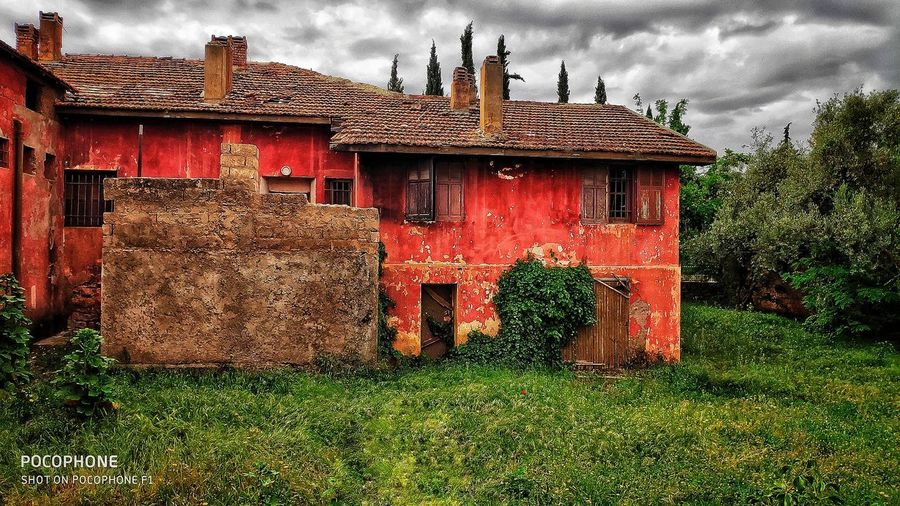 Red house on field against sky