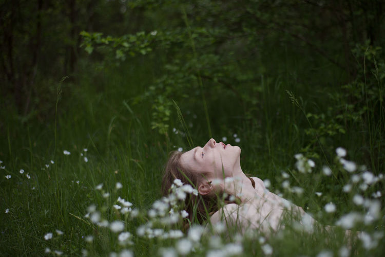 Midsection of woman relaxing on field