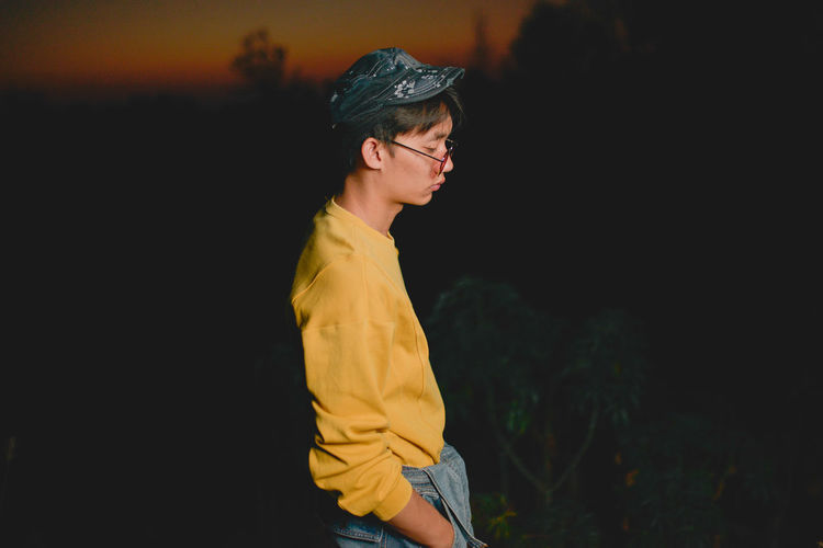 Side View Of Young Man Wearing Sunglasses Standing Against Sky At Dusk