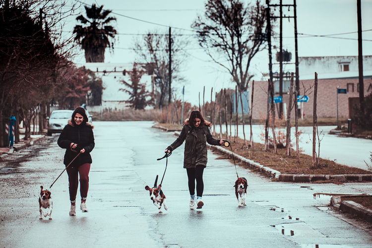 People with dog on snow during winter