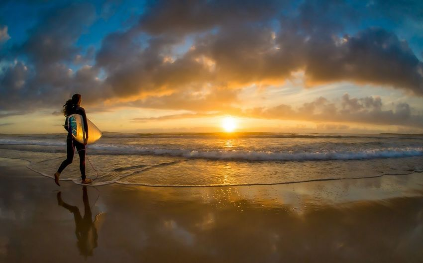 Full length of woman with surfboard walking on beach during sunset