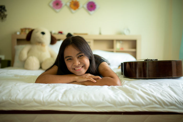 Asian girl in bed sleeping Guitar Bedroom Portrait Pillow Smiling Bed Domestic Room Domestic Life Happiness Cheerful Relaxation Quilt Night Table Sole Of Foot Side Table Turning On Or Off Lamp Shade  Human Toe Duvet Double Bed Alarm Clock Electric Lamp Waking Up Camisole Bedtime Hotel Room Motel Hotel Suite