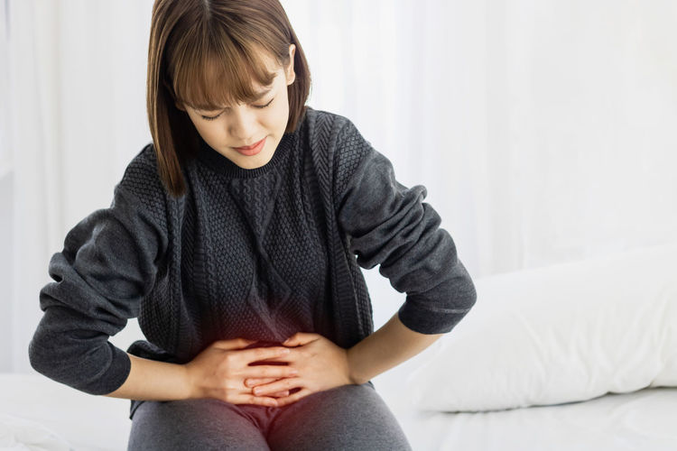 Woman with stomachache sitting on bed at home