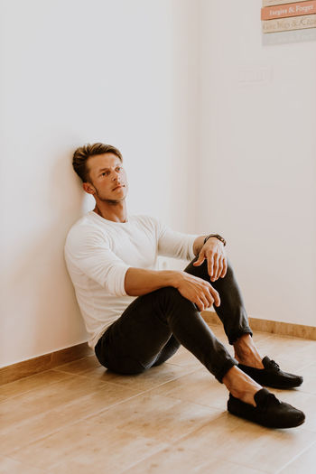 Full length of man looking away while sitting on hardwood floor against wall