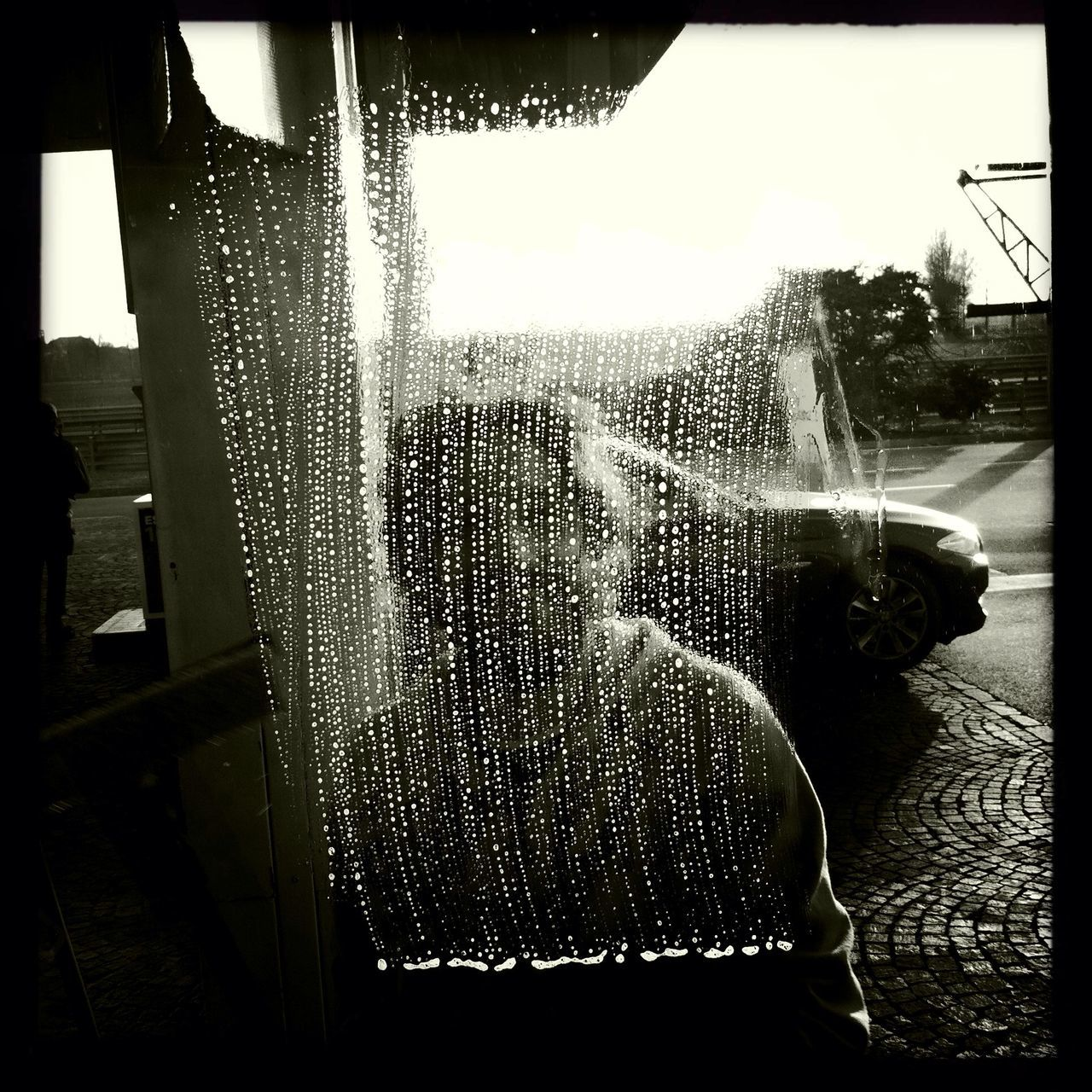 Man seen through wet glass window