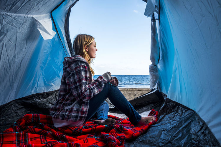 Side view of young woman sitting in tent at beach