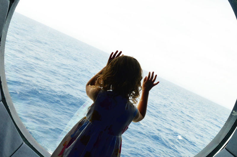 Girl Looking Through Window Against Sea