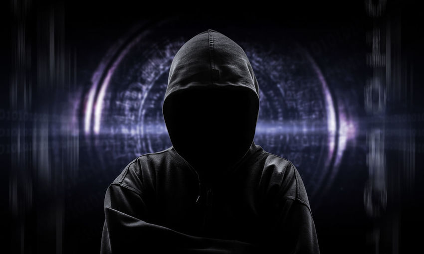 Computer hacker in hooded shirt against interface