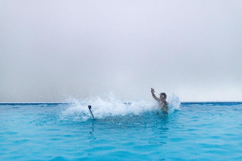 Young man splashing water in infinity pool