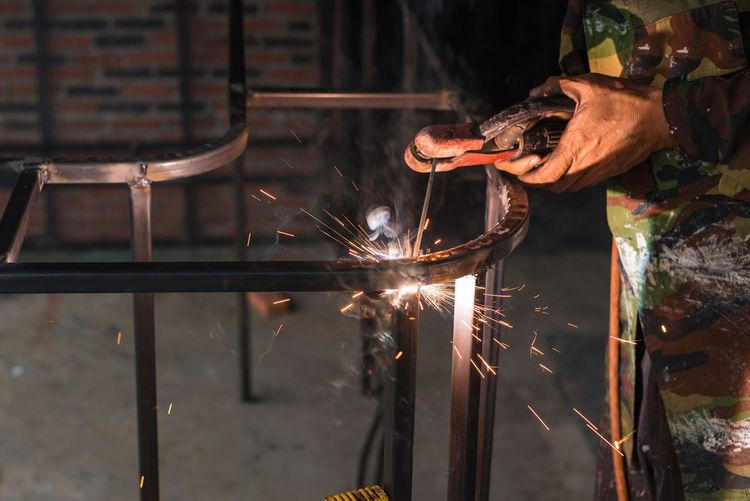 Midsection of worker welding metal in workshop