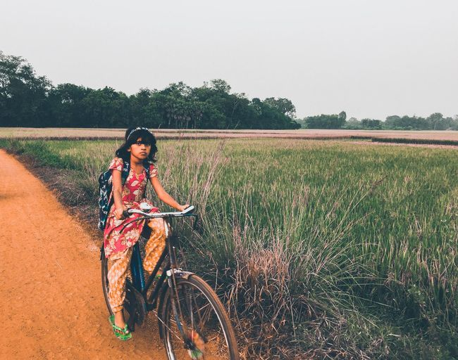 Woman riding bicycle on field