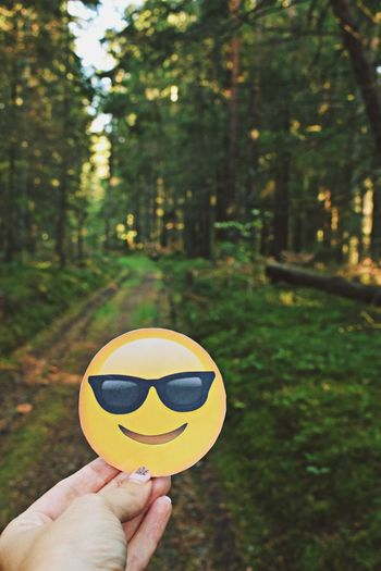 Body Part Concept Day Emoticon Emotion Finger Focus On Foreground Forest Hand Holding Human Body Part Human Finger Human Hand Land Leisure Activity Lifestyles Nature One Person Outdoors Personal Perspective Plant Real People Sunglasses Tree Unrecognizable Person