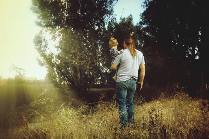 Rear view of man carrying baby on countryside landscape