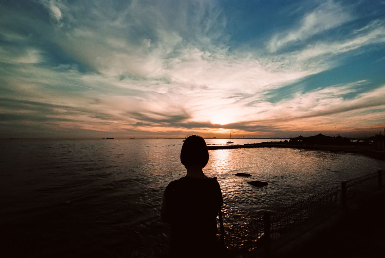Silhouette of person on beach against cloudy sky at sunset