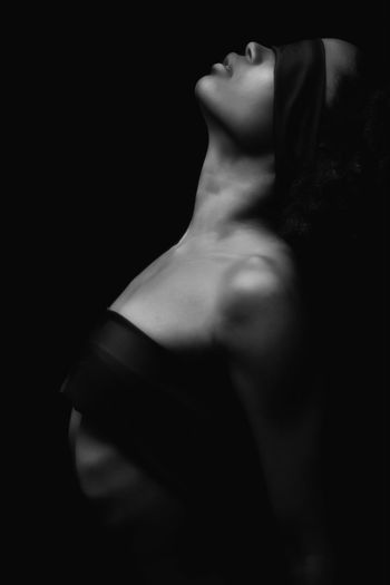 Side View Of Sensuous Woman With Ribbons Against Black Background