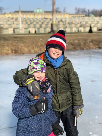 Portrait Of Siblings In Warm Clothing Standing On Ice Rink