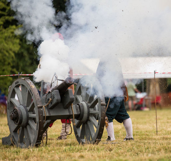 Man with cannon emitting smoke on field