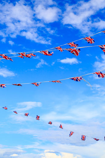 Bunting Blowing In The Wind  Celebration Patriotic Beauty In Nature Bunting Cloud - Sky Day Flag Hanging Low Angle View National Flag Nature No People Outdoors Party Red Sky Skyscraper Streamer Union Jack Wind