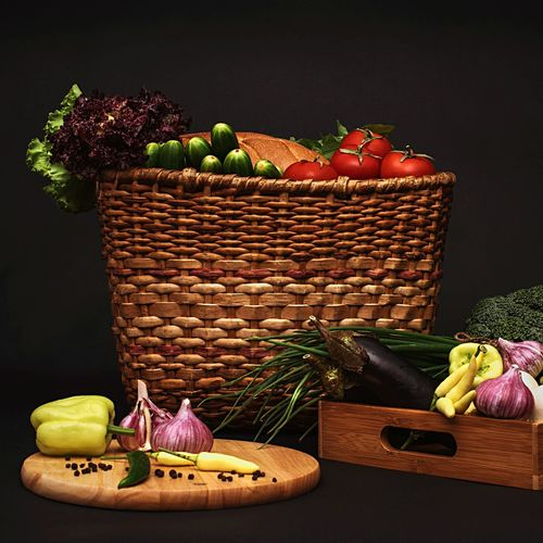 Fresh vegetables on basket and cutting board against black background