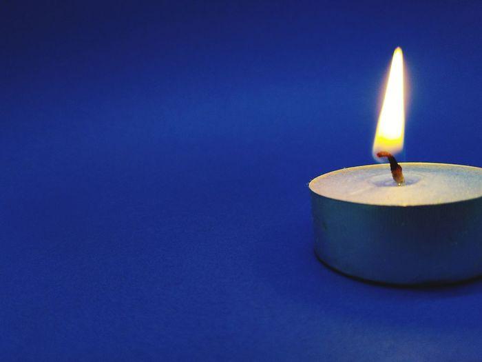 Close-Up Of Illuminated Tea Light On Blue Background