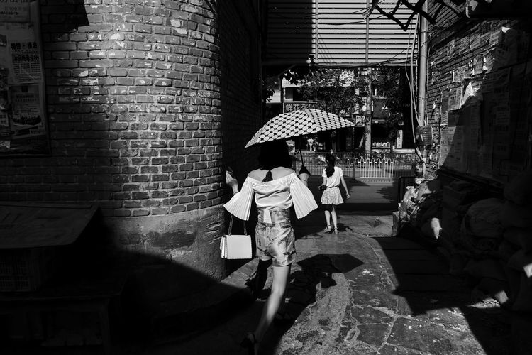 light and women Blackandwhite Lght And Shadow Architecture Built Structure Real People Umbrella Lifestyles Building Exterior The Street Photographer - 2018 EyeEm Awards Women People Day Brick Building Walking Brick Wall Wall