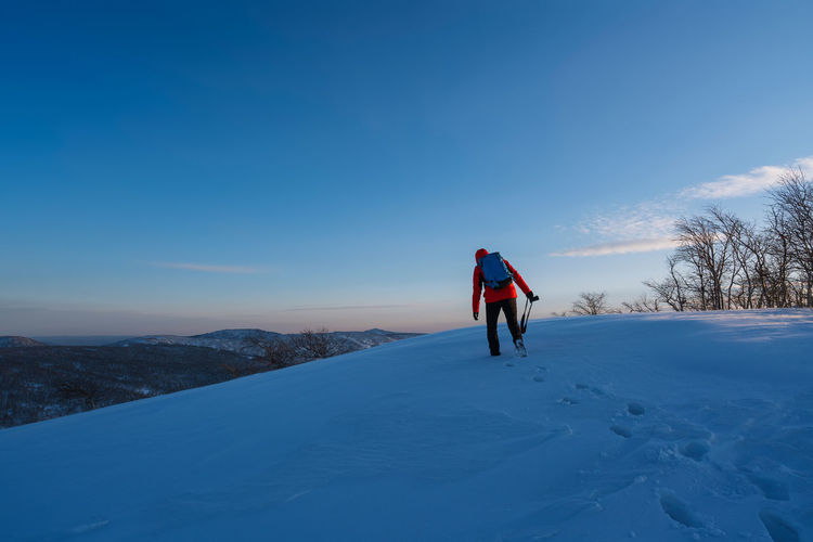 Rear view of person standing on snow against sky