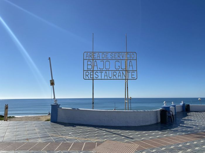 Information sign by sea against clear blue sky