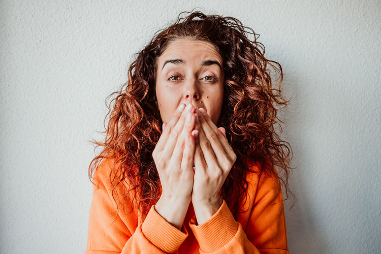 Portrait of woman sneezing while standing against wall