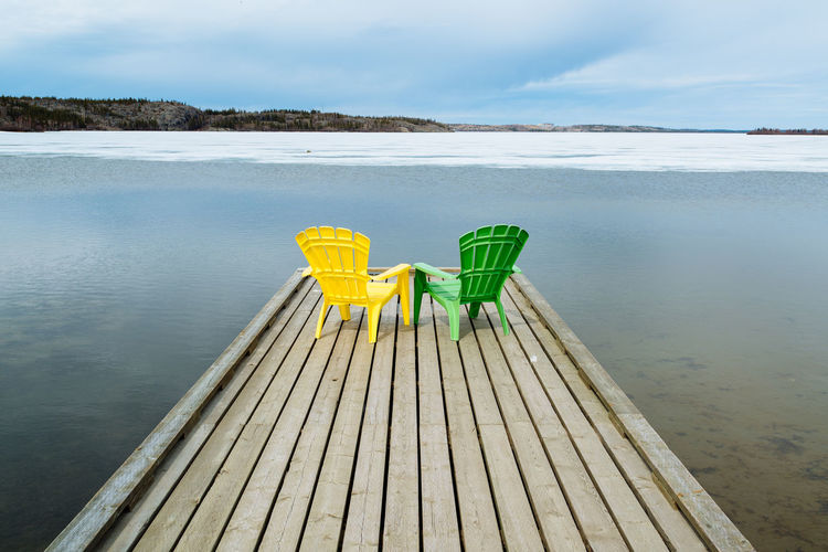 Green And Yellow Adirondack Chairs On Pier At Lake During Winter