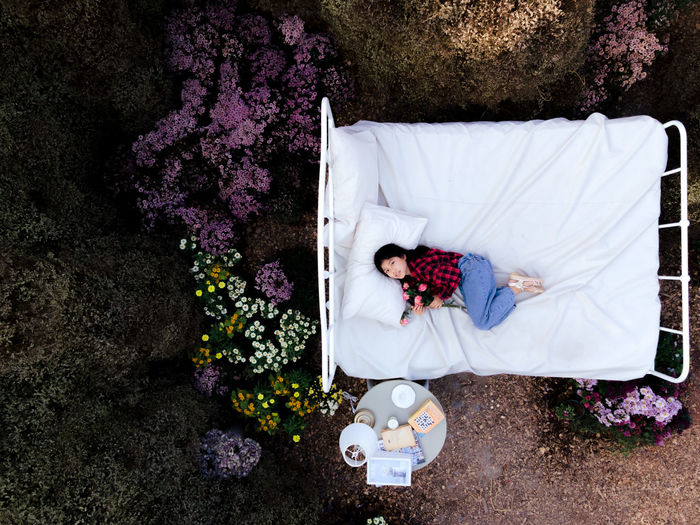 Drone shot of girl lying on bed amidst trees in forest