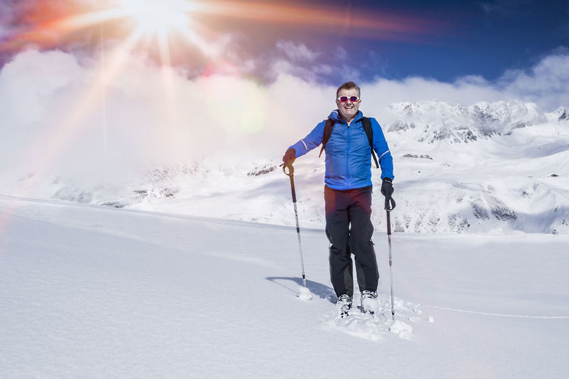 Full Length Of Smiling Man Standing On Snow Covered Landscape
