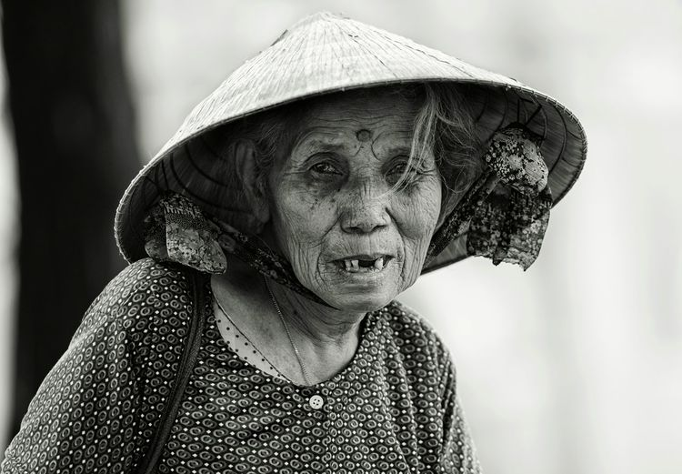 Close-up portrait of senior woman wearing hat standing outdoors