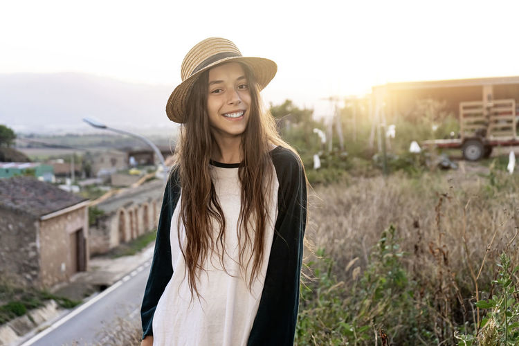 Smiling young woman wearing hat standing against building