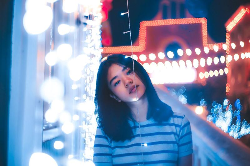 Portrait Of Young Woman With Head Cocked By Illuminated String Lights At Night