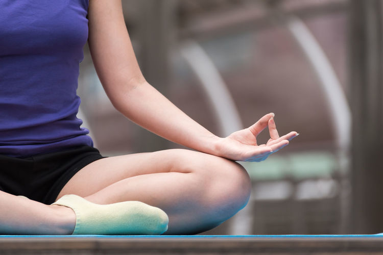 Low section of woman practicing yoga while sitting outdoors