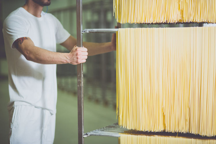 Midsection of worker pushing trolley fresh spaghetti in factory