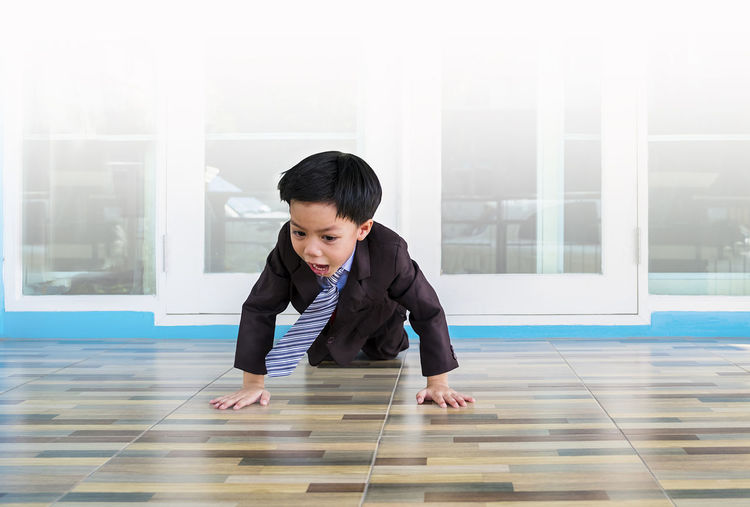 Boy shouting while crawling on tiled floor